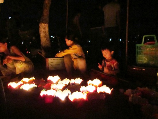 Một bé trai tỏ ra thích thú khi ngắm đèn lồng tại Hội An.  Vào ngày 14 hoặc chính rằm, người dân đã tấp nập đến chùa lễ Phật, cầu bình an, khoẻ mạnh, hạnh phúc… cho cả năm. Ngoài tới chùa, người Việt cũng rất coi trọng lễ cúng tại nhà.