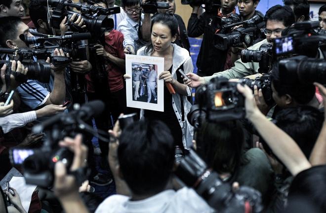 """Một thân nhân hành khách của chuyến bay MH370 cầm ảnh in hình Thủ tướng Malaysia Najib Razak với thông điệp """"Hãy mang chồng của tôi trở về""""."""