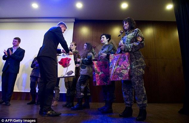 Nu binh si Ukraine buong sung, buoc len san dien thoi trang hinh anh 12 Sau màn trình diễn, đại diện chính quyền đã tặng hoa và quà cho các cô gái trong sự kiện chào mừng ngày Quốc tế phụ nữ. Ảnh: AFP