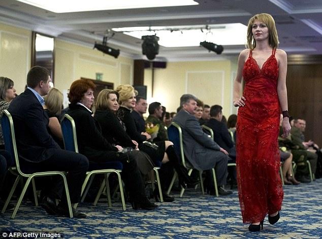 Nu binh si Ukraine buong sung, buoc len san dien thoi trang hinh anh 2 Để tham gia sự kiện trong ngày đặc biệt dành cho phái đẹp, các cô thay bộ quân phục thường ngày và khoác lên những chiếc váy dạ hội lộng lẫy. Ảnh: AFP