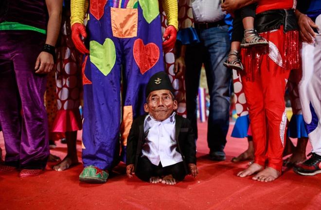 Chandra Bahadur Dangi (72 tuổi) chụp ảnh cùng nhiều nghệ sĩ của gánh xiếc Rambo tại Mumbai, Ấn Độ. Với chiều cao 54,6 cm, Dangi là người đàn ông lùn nhất thế giới. Ảnh: Reuters