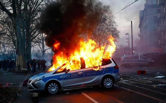 Nhiều người biểu tình phóng hỏa một xe cảnh sát bên ngoài Ngân hàng Trung ương châu Âu (ECB) trước lễ khai trương tòa nhà mới tại Frankfurt, Đức. Hành động của họ nhằm phản đối chính sách thắt lưng buộc bụng.  Ảnh: Reuters