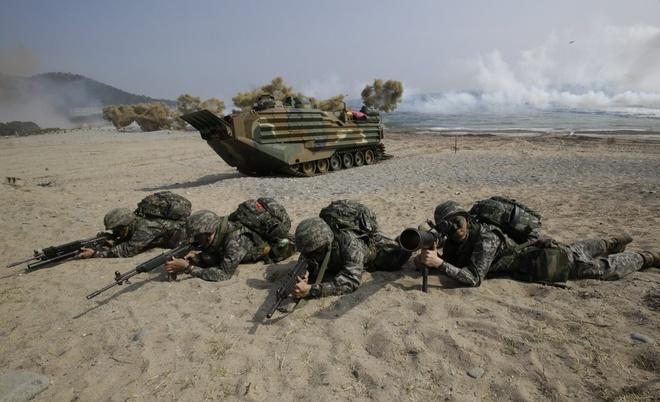Binh sĩ Hàn Quốc vào vị trí nhắm bắn trong cuộc tập trận, đằng sau họ là một xe đổ bộ tấn công của hải quân. Chính phủ Hàn Quốc và quân đội Mỹ luôn khẳng định mục đích tập trận chỉ để nâng cao phòng thủ.