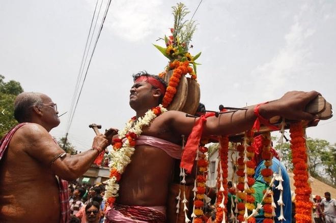 Dong dinh vao tay, xoa chan len mat de cau may o An Do hinh anh 7 Một chức sắc tôn giáo đang đóng đinh xuyên qua cánh tay của một người mộ đạo. Họ mong muốn thần Shiva trong đạo Hindu sẽ đáp ứng những lời cầu nguyện.