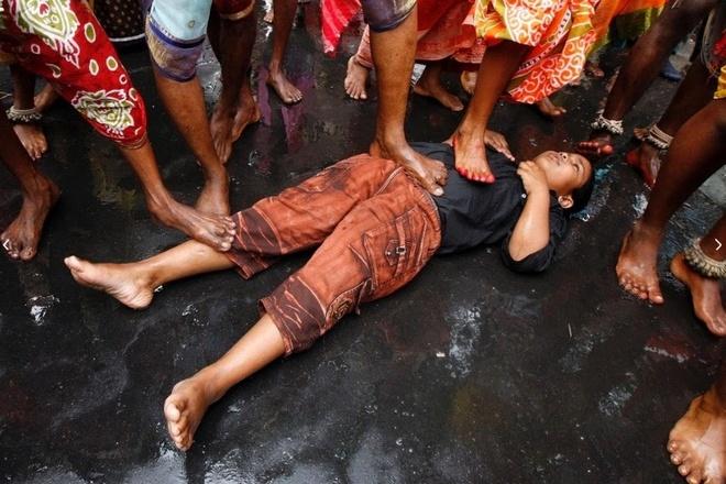 Dong dinh vao tay, xoa chan len mat de cau may o An Do hinh anh 4 Nhiều gia đình đặt trẻ con nằm sẵn trên đường để chờ các vị giáo sĩ đi qua và làm phép cầu may mắn. Các bé gái hào hứng theo dõi hoạt động của các giáo sĩ.