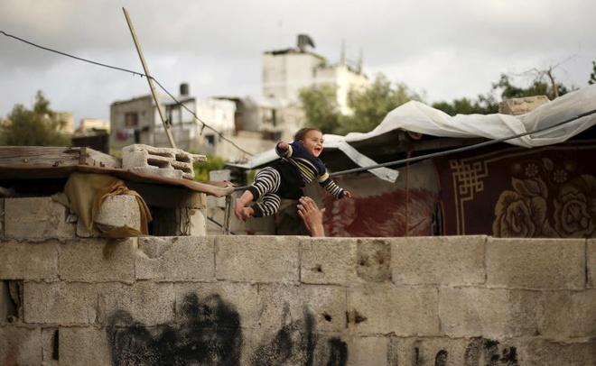 Loat anh an tuong nhat tuan (13 - 19/4) hinh anh 9 Người đàn ông Palestine chơi với con trai nhỏ bên ngoài ngôi nhà bị tàn phá bởi bom đạn ở thị trấn Biet Lahiya, dải Gaza.