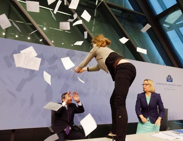 Loat anh an tuong nhat tuan (13 - 19/4) hinh anh 3 Khi ông Draghi, Chủ tịch Ngân hàng Trung ương châu Âu, đang phát biểu trong trụ sở của ngân hàng tại thành phố Frankfurt, Đức hôm 15/4, Josephine Witt, một người phụ nữ, bất ngờ nhảy lên bàn rồi ném hoa giấy về phía ông