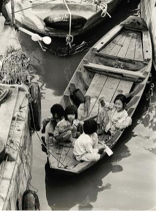 Tre em trong chien tranh Viet Nam qua anh quoc te hinh anh 1 Những đứa trẻ vui đùa trên thuyền ở một dòng kênh tại Sài Gòn, ngày 3/10/1965. Ảnh: AP