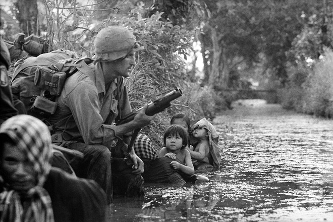 Tre em trong chien tranh Viet Nam qua anh quoc te hinh anh 3 Hai em nhỏ Việt Nam ngước nhìn một lính dù Mỹ đang cầm súng phóng lựu M79 tại khu vực Bảo Trai, cách Sài Gòn 32 km.