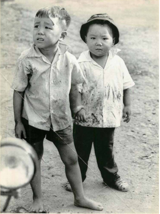 Tre em trong chien tranh Viet Nam qua anh quoc te hinh anh 10 Hai bé trai nắm tay nhau hòa cùng dòng người di tản khỏi Chợ Lớn, Sài Gòn, ngày 13/5/1968. Ảnh: UPI