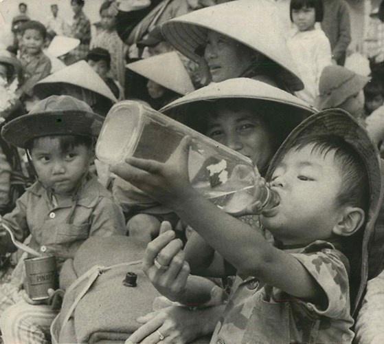 Tre em trong chien tranh Viet Nam qua anh quoc te hinh anh 12 Trong cơn khát, một bé trai uống nước từ chai rượu cũ. Cậu bé cùng gia đình đang tập trung tại một sân bóng ở Kom Tum để chờ di tản khỏi vùng chiến sự, ngày 7/6/1972. Ảnh: AP