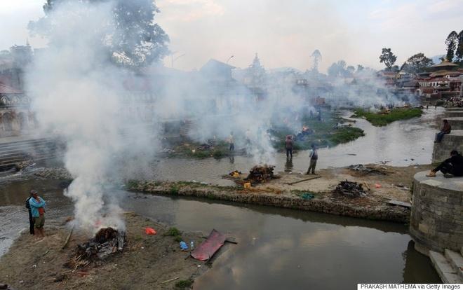 Người dân Nepal hỏa thiêu các nạn nhân của trận động đất trong một lễ tang tập thể tại đền Pashupatinath, cạnh bờ sông Bagmati, hôm 26/4. Trận động đất mạnh 7,9 độ Richter làm rung chuyển khu vực nằm giữa thành phố Pokhara và thủ đô Kathmandu. Hơn 3.200 người đã thiệt mạng sau cơn địa chấn. Ảnh: AFP