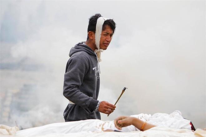 Một thanh niên làm lễ trước thi hài mẹ. Ảnh: AP