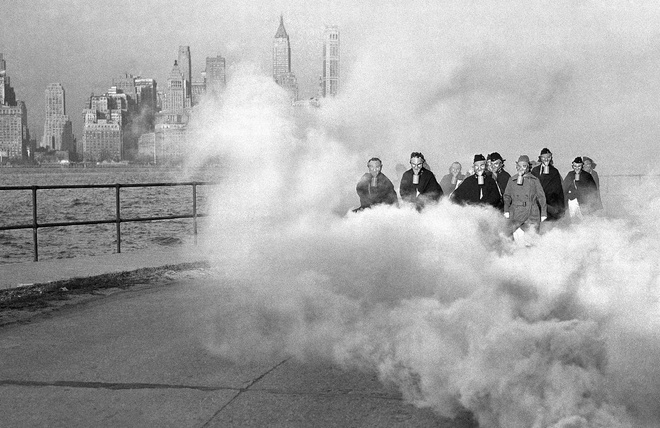 Nhiem vu cua phu nu trong The chien II hinh anh 4 Nhóm nữ quân y của một bệnh viện ở Fort Jay trên đảo Governors, thành phố New York, đeo mặt nạ khí trong buổi diễn tập các biện pháp bảo hộ, ngày 27/11/1941. Phía xa, những tòa nhà chọc trời chìm trong những đám mây khí.