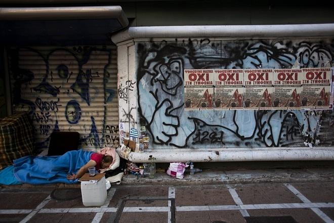 """Người đàn ông vô gia cư ngủ trước cổng một cửa hàng dán tấm áp phích với từ """"Không"""" - câu trả lời từ chối điều khoản của các chủ nợ châu Âu - ở thủ đô Athens, Hy Lạp. Bộ trưởng Tài chính Hy Lạp, ông Yanis Varoufakis, từ chức sau cuộc trưng cầu với đa số cử tri nói """"Không"""" với các biện pháp thắt lưng buộc bụng hơn để đổi lấy một gói cứu trợ tài chính từ châu Âu."""