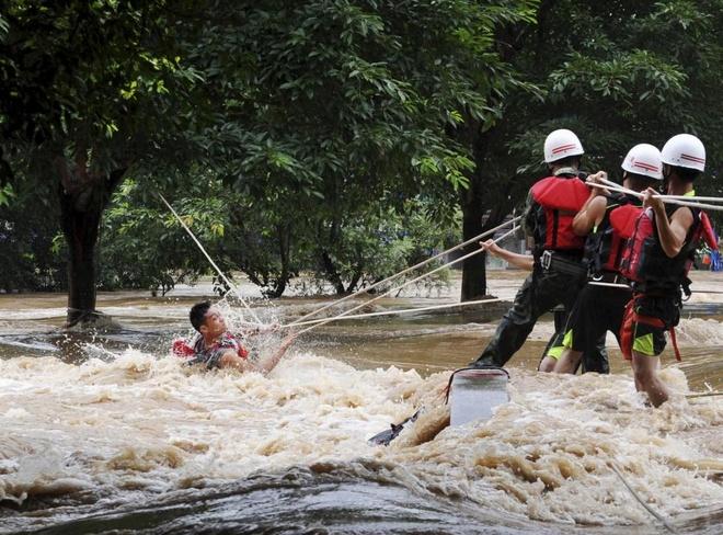 Nhân viên cứu hộ Trung Quốc dùng dây kéo một người đàn ông mắc kẹt trên đường sau trận mưa lớn trên sông Lệ Giang, tỉnh Quế Lâm, khu tự trị Quảng Tây, hôm 2/7.