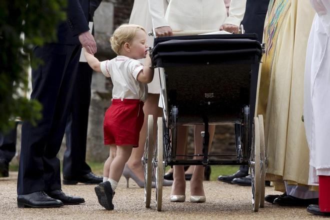 Hoàng tử bé George của Anh nhún chân để nhìn em gái - Công chúa Charlotte - đang nằm trong xe nôi, sau lễ rửa tội tại nhà thờ St. Mary Magdalene hôm 5/7. Nhà thờ tọa lạc trong khu đất Sandringham của Nữ hoàng Anh ở hạt Norfolk.