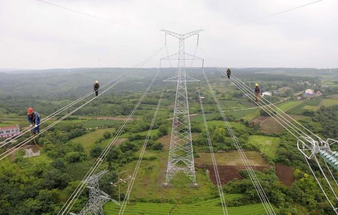 Các công nhân cố gắng giữ thăng bằng khi kiểm tra đường dây điện mới ở thành phố Chuzhou, tỉnh An Huy, Trung Quốc hôm 9/7.