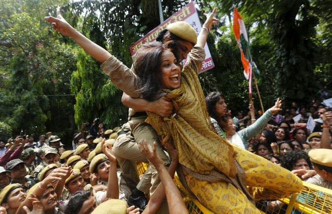 Nhung hinh anh an tuong nhat tuan qua (20 - 26/7) hinh anh 4 Một nữ cảnh sát cố gắng ngăn thành viên của All India Mahila - một phe cánh của phụ nữ thuộc đảng Quốc Đại Ấn Độ - vượt qua chướng ngại vật trong cuộc biểu tình chống Thủ tướng  Narendra Modi ở thủ đô New Delhi, hôm 21/7.
