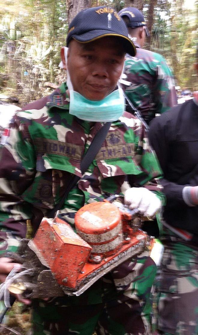 Hien truong phi co Indonesia dam vao nui hinh anh 5 Binh sĩ Indonesia cầm thiết bị ghi dữ liệu chuyến bay của phi cơ được tìm thấy tại hiện trường.