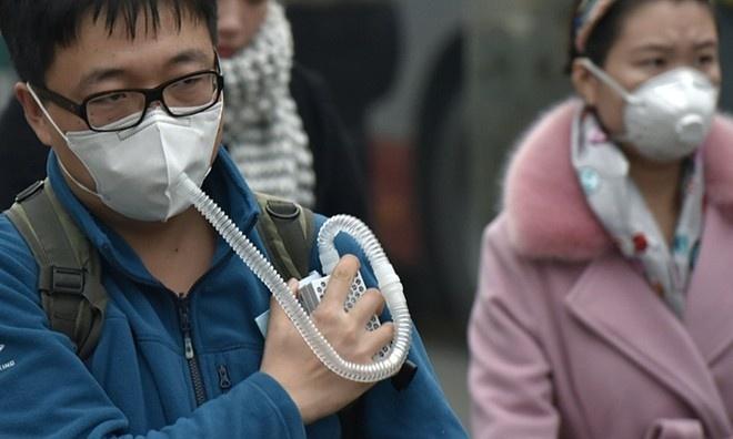 Một thanh niên mang theo máy hô hấp khi di chuyển qua trung tâm ở Bắc Kinh khi sương dày. Ảnh: Getty