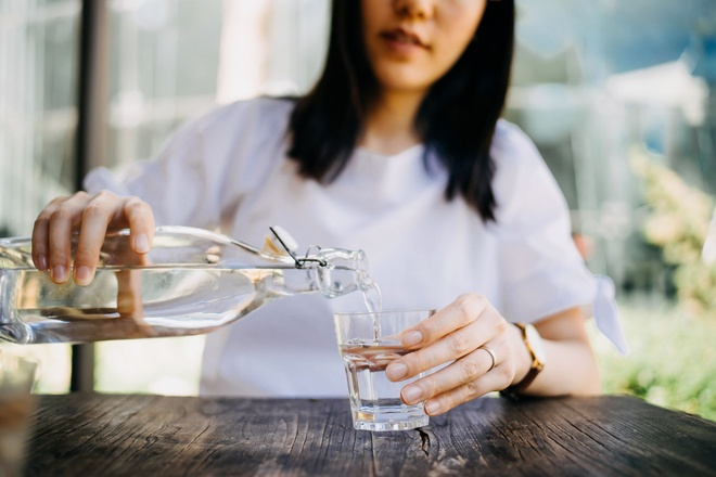 Bi quyet giai nhiet co the cap toc trong mua he hinh anh 1 woman_pouring_water_from_bottle_into_the_glass_at_a_royalty_free_image_1584561316.jpg