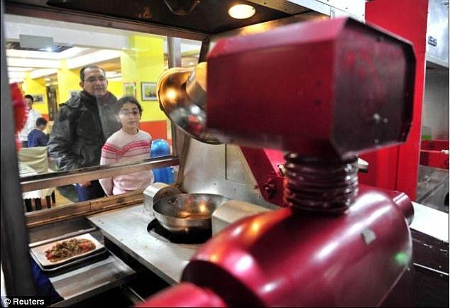 Robot lam nhan vien nha hang o Trung Quoc hinh anh 3 Khách hàng quan sát robot nấu ăn. Các robot có thể chào hỏi, trò chuyện với khách hàng bằng 40 cụm từ.