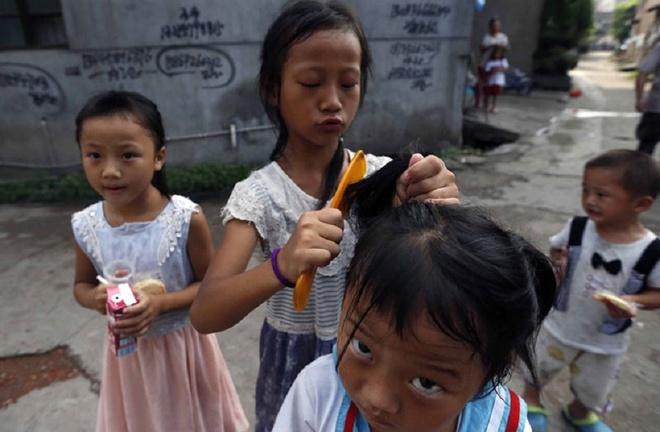 Cuoc song khong thit cua gia dinh 9 nguoi o Trung Quoc hinh anh 6 Cô con gái riêng của Yue chải tóc cho em gái cùng mẹ khác cha. Em bị cậ thị nặng nhưng gia đình không thể trả 380 tệ để mua cho em một cặp kính.