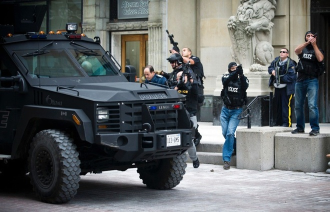 Loat anh ngoan muc nhat trong nam 2014 (ky 4) hinh anh 10 Lực lượng an ninh hộ tống các quan chức cấp cap khi các tay súng tấn công Tòa nhà Quốc hội trên đường Sparks, thành phố Ottawa, Canada, hôm 22/10/2014. Ảnh: Postmedia/ Barcroft