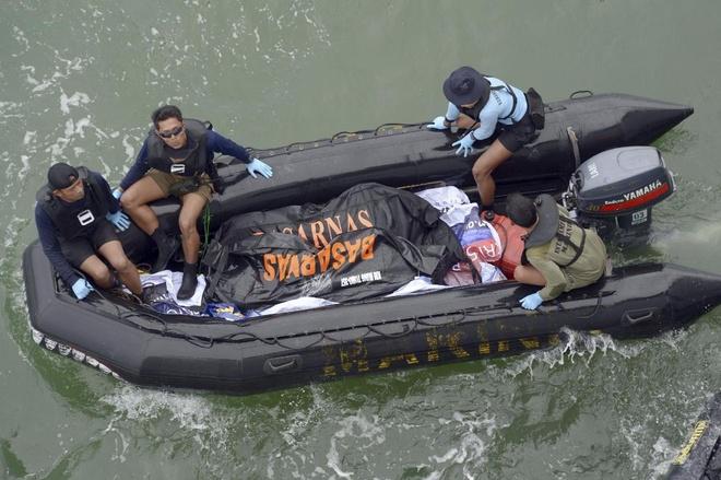 Indonesia chua the vot duoi cua may bay do thoi tiet xau hinh anh 1 Thợ lặn quân đội Indonesia vớt một thi thể nạn nhân trên chuyến bay QZ8501 trên Biển Java hôm 9/1. Ảnh: AP