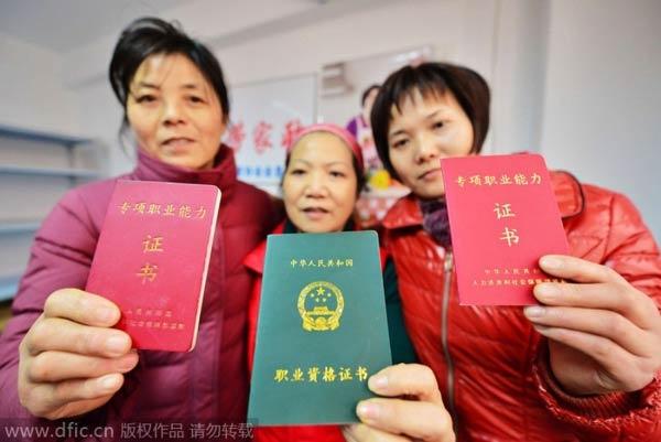 3 phụ nữ giơ chứng chỉ nghề bảo mẫu trong một trung tâm giới thiệu việc ở Thượng Hải.