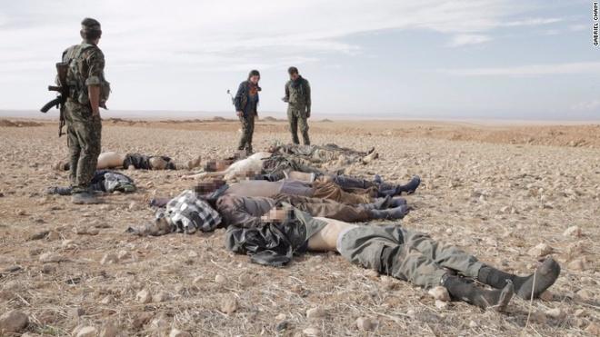 Chiến binh người Kurd rà soát và kiểm tra thiết bị nổ trên người của phiến quân sau cuộc đối đầu. Ảnh: