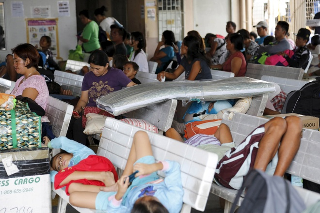 720.000 người ở vùng Bicol đã sơ tán từ cuối tuần để tránh bão. Trong ảnh là hành khách bị mắc kẹt ở cảng Hagnaya, phía bắc đảo Cebu hôm 14.12. Ảnh: Reuters