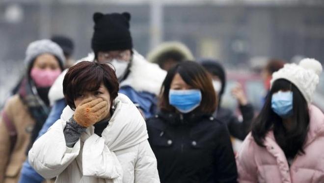 Bac Kinh tiep tuc bao dong do o nhiem khong khi hinh anh 1 Người dân Bắc Kinh đeo khẩu trang khi đi ra đường hôm 8/12. Ảnh: AP
