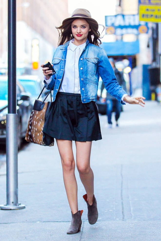 Hoc sao cach dien vay vao mua dong hinh anh 6 Siêu mẫu Miranda Kerr cực chất với áo khoác bò, sơ mi trắng phối với chân váy xếp ly đen dáng xòe.