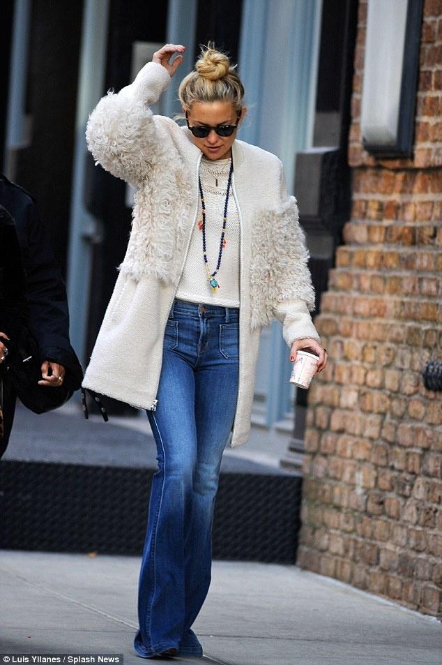 3 kieu ao khoac dang dai duoc sao ngoai yeu thich hinh anh 6 Kate Hudson năng động và cá tính với áo len trắng, quần jeans ống loe cùng áo khoác len lông cừu màu trắng thanh lịch bên ngoài.
