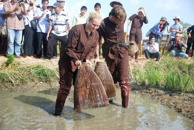 Khach Tay chan lam tay bun lam nong dan Viet hinh anh 2 Những ông tây lội bùn xuống ruộng đơm cá. Ảnh thethaovanhoa