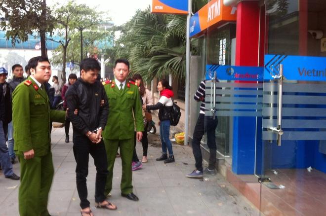 Cao thu trom tien ty o nhieu cay ATM hinh anh 1 Đại (giữa) bị cảnh sát dẫn giải chỉ vị chỉ 2 cây ATM định trộm bên phố Nguyễn Chí Thanh.