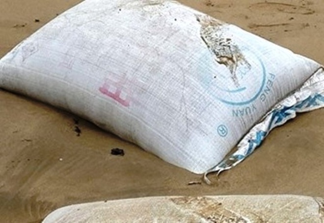 Nhieu bao tai chua bot la co mui hoi dat vao bien Thanh Hoa hinh anh 1 Một trong hàng trăm bao tải chứa chất lạ trôi dạt vào bờ biển Thanh Hóa.