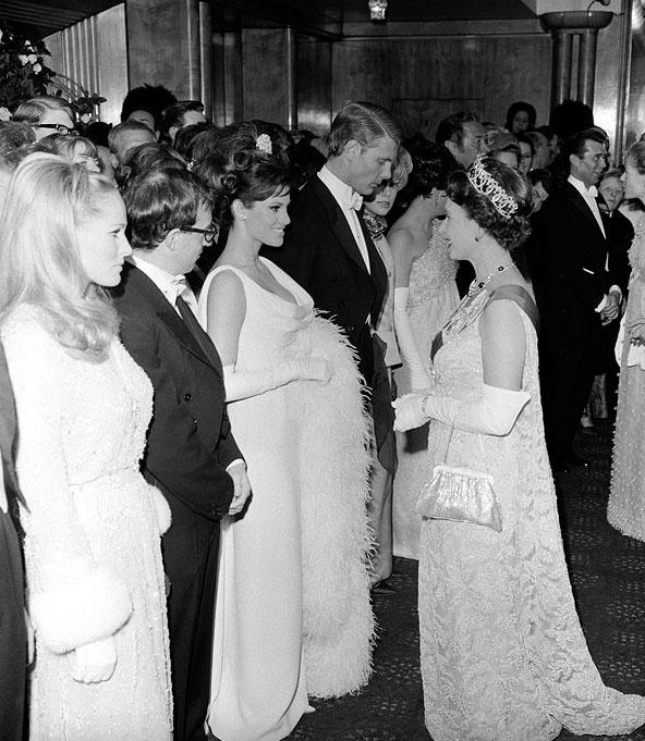 Ngam phong cach Nu hoang Anh khi gap sao hang A Hollywood hinh anh 25 Chiếc váy cùng trang sức quý phái của Nữ hoàng khi bà gặp nam diễn viên nổi tiếng Woody Allen (người đeo kính thứ hai từ trái sang hàng đầu tiên). Trong ảnh, Nữ hoàng đang nói chuyện với Raquel Welch (bên trái Woddy Allen), còn nữ diễn viên Ursula Andress thì đứng bên phía phải của Woody