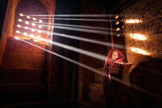 An tuong anh doat giai 'Anh du lich 2014' hinh anh 5 Bức ảnh Nguồn sáng chụp cảnh một chú tiểu tìm nơi có ánh sáng tốt nhất để đọc sách tại ngôi chùa ở Old Bagan, Myanmar. Tác giả: Marcelo Castro - National Geographic