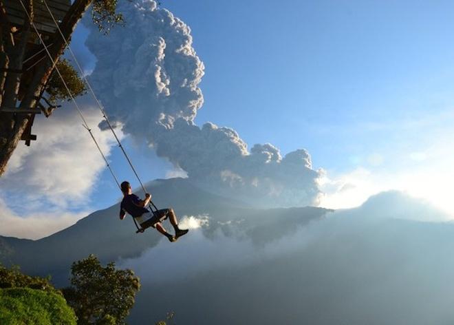 An tuong anh doat giai 'Anh du lich 2014' hinh anh 6 Nơi tận cùng thế giới ở Banos, Ecuador chụp lại cảnh một người đàn ông ngồi trên xích đu nhìn về ngọn núi lửa Tungurahua đang phun trào. Sau vài phút chụp tấm ảnh này, tác giả đã phải sơ tán do một đám mây bụi tràn đến. Tác giả: Sean Hacker Teper - Ảnh: National Geographic