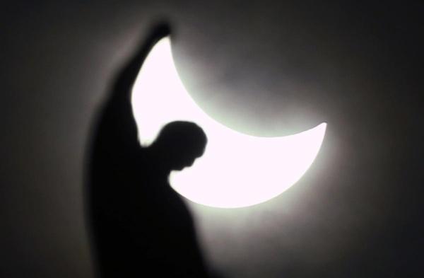 Hiện tượng nhật thực nhìn từ phía sau một bức tượng nhà thờ Gothic Duomo ở Milan, Italy ngày 20/3.