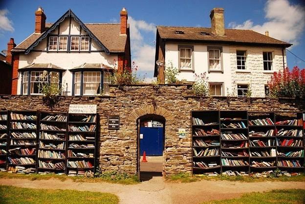 """Hiệu sách Honesty Bookshop của Hay-on-Wye, thị trấn Welsh, Anh: Thường được mô tả như là """"thị trấn của cuốn sách"""", Hay-on-Wye thu hút một số lượng lớn những người yêu sách đến đây tìm kiếm trong hơn 40 nhà sách, chủ yếu là sách cũ.  Trong số nhiều hiệu sách, nổi tiếng và thú vị nhất là """"Honesty Bookshops"""" – hiệu sách trung thực. Ở đó chỉ là hai kệ sach đặt ở bên tường và không có người trông coi. Mọi người đến đơn giản là chọn sách và trả tiền và một hộp thư nhỏ. Hiệu sách nằm trong phần đất của pháo đài Hay, một pháo đài có từ thế kỷ 12 năm ở trung tâm thị trấn. Không gian sách ngoài trời này bao gồm các kệ gỗ, đặt cạnh các bức tường."""