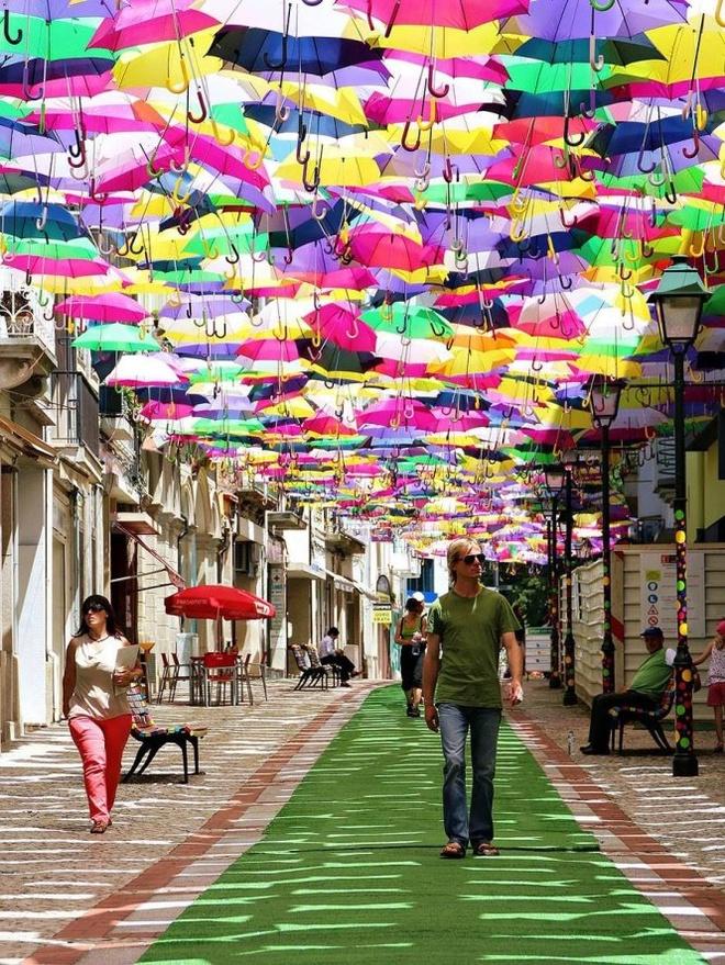 Chiem nguong 'bau troi o du' day sac mau o Agueda hinh anh 2 Họ đến để hòa mình vào không khí náo nhiệt của lễ hội nghệ thuật Agitagueda, nhất là để tản bộ dưới những tán dù lấp lánh sắc màu trên phố...