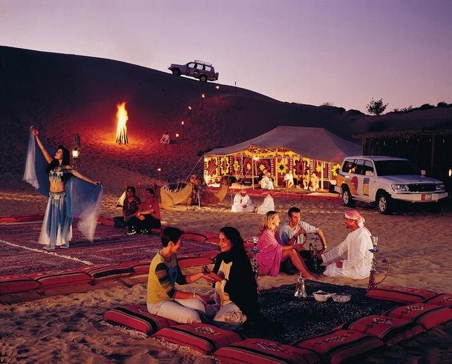 """Tour tron goi kham pha ve dep Abu Dhabi - Dubai hinh anh 8 Buổi chiều bạn sẽ đi vào trung tâm của sa mạc và tham qua """"Desert safari tour"""", đó là trải nghiệm trên xe Land Cruiser băng qua những ngọn dốc cao vút của sa mạc, sau đó là thưởng thức tiệc đồ nướng trong những túp lều dựng bằng lá cọ khô, cưỡi lạc đà và xem những tiết mục múa bụng truyền thống. Ảnh: Jcholidays.com.au."""