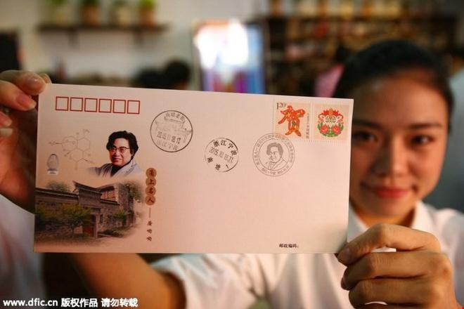 Nha cua nguoi gianh giai Nobel y hoc thanh diem du lich hinh anh 3   Một nhân viên giới thiệu một phong bì có dán tem kỷ niệm với hình ảnh của Đồ U U và nơi ở cũ của bà ở Ninh Ba.