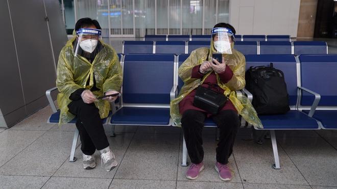 Người dân Bắc Kinh mặc áo mưa, đeo khẩu trang và mặt nạ nhựa tự chế. Ảnh: CNN.