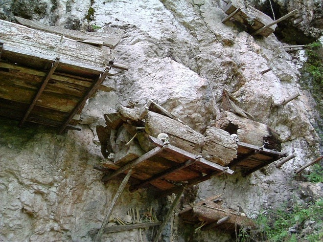 Một cách an táng khác là bỏ xác chết vào quan tài bằng gỗ rồi treo trên vách đá. Các cỗ quan tài thường được trang trí cầu kỳ. Qua thời gian, gỗ quan tài bị mục, hài cốt rơi xuống và lẫn vào trong đất.