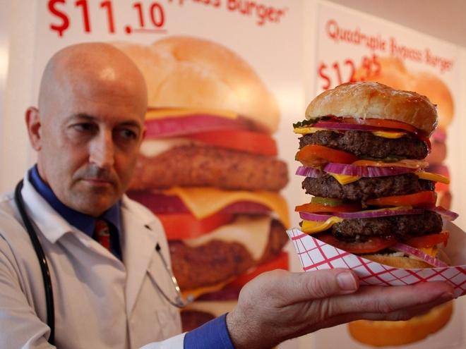 Nhung nha hang hut khach voi phong cach quai chieu hinh anh 15 Ông chủ nhà hàng Heart Attack Grill đang tạo dáng cùng một chiếc bánh burger phô mai ở Chandler, Arizona năm 2009. Nhà hàng mang chủ đề bệnh viện, còn thực khách được mặc những bộ đồng phục bệnh viện khi vào ăn bánh burger. Nhà hàng sau đó đóng cửa và chuyển đến Las Vegas.